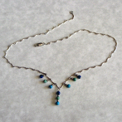 Curved link chain with wrapped loop drops of small lapis lazuli, turquoise and green agate beads.